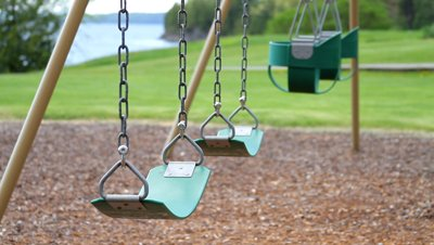 stock-footage-empty-swings-in-waterside-park