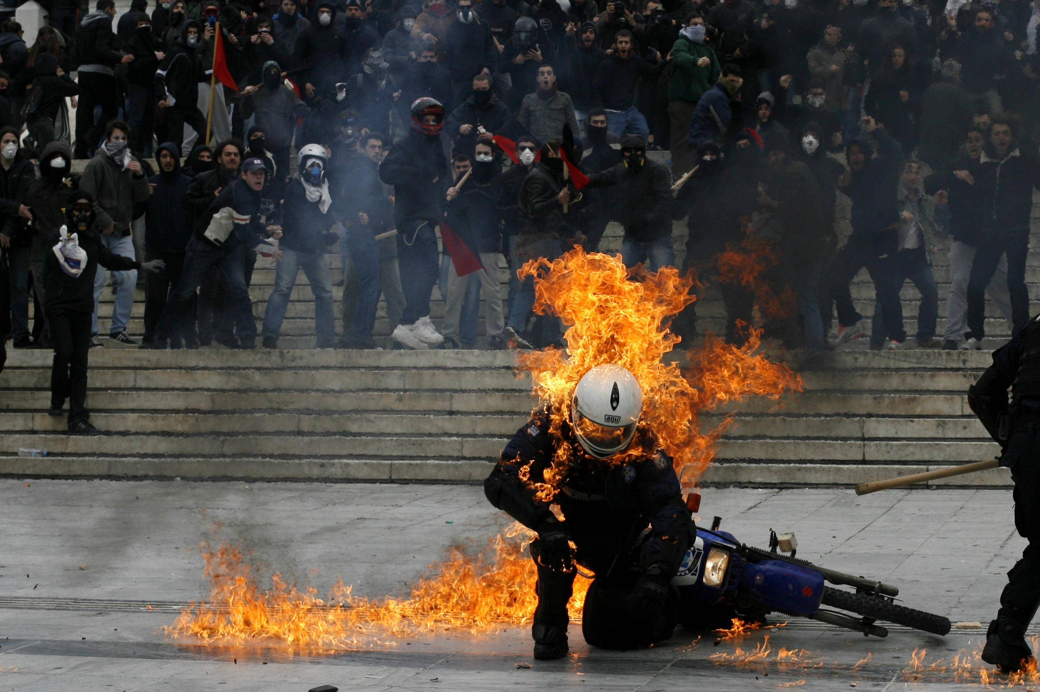Greek police fire tear gas at masked protesters wielding gas bombs during anti-austerity rally in central Athens.