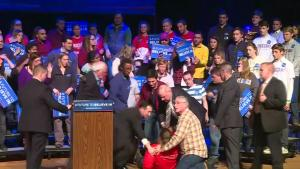 A woman fainted at a Bernie Sanders rally in New Hampshire, but was able to walk away. Rough Cut (no reporter narration).