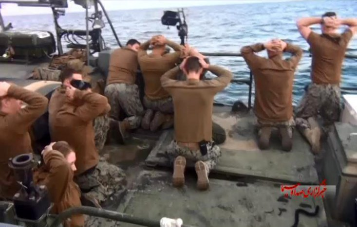 This picture released by the Iranian state-run IRIB News Agency on Wednesday, Jan. 13, 2016, shows detention of American Navy sailors by the Iranian Revolutionary Guards in the Persian Gulf, Iran. Iranian state television is reporting that all 10 U.S. sailors detained by Iran after entering its territorial waters have been released. Iran's Revolutionary Guard said the sailors were released Wednesday after it was determined that their entry was not intentional. The nine men and one woman were being held at an Iranian base on Farsi Island in the Persian Gulf after being detained nearby on Tuesday.(Sepahnews via AP)